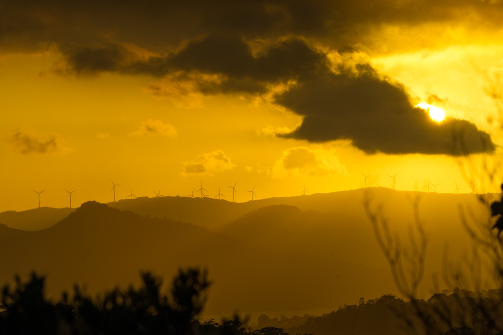 Sunset looking west above lake Arenal. Large wind farm on the ridge.