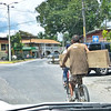 A common site in Liberia (carrying lumber, kids, the entire family, on bike)