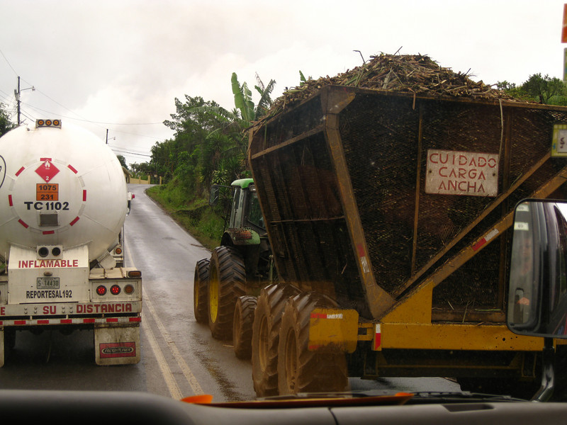 Two large vehicles on the main north south highway between Nicaragua and Panama, the Pan American Highway.  One is carrying flammable fuel and the other freshly harvested sugar cane