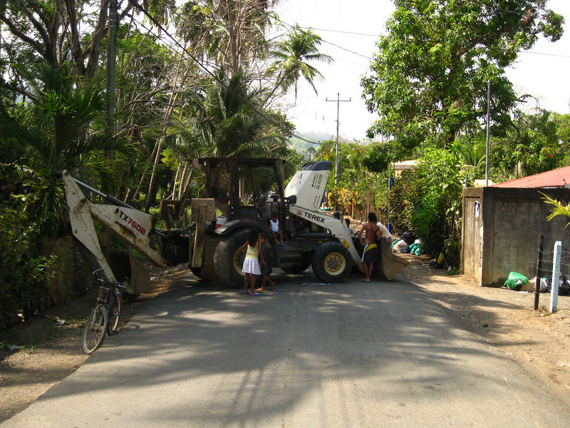 An interesting situation...this earth mover broke down in the middle of the road outside Puntarenas, CR.  Basically the traffic is stopped in either direction until the local garbage truck, that's right, garbage truck can come and tow it away...
