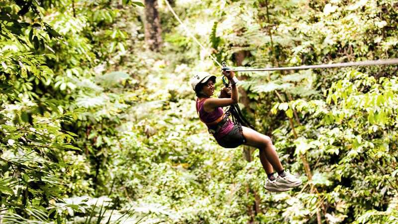 """Zip-lining in Costa Rica.  Checked out of Playa Espadilla hotel in Manuel Antonio @8am, heading to Herradura near the Jacos beach for a Zip-lining experience.  <a href=""""http://www.canopyvistalossuenos.com/"""">Vista Los Suenos Canopy Tour</a> in Herradura runs a zip-lining operation with 13 cables, the longest about 2400 feet. We were strapped into our harness, signed a waiver, then 16 of us started out in a blue tractor that drove up a mountain road to the beginning of the first cable. We were given preliminary instructions & we started off. V & K were in Group 1. So V was the team leader, group leader, and the first person to zip for the day!!!  Zip-lining is absolutely awesome! You are flying on top of the trees, much faster than birds & at a much higher elevation. You put the stronger hand behind you on the cable, hold on to the three safety cables with the weak hand, and let go. The pulley on the cable & the gravity does the rest. You arrive at a tremendous speed at the next platform, where the cables are taken off, & you then go around the tree to the next cable which leads you to the next platform & so on, on & on for 12 cables!  It takes about 2 hours, and leaves you wanting for lots more! If we had done this on Day 1, we would certainly have repeated this several times during our stay. However, this being our last day in CR, memories & videos will have to suffice.   Zip-lining was certainly our most favorite activity in CR & we look forward to doing it again."""