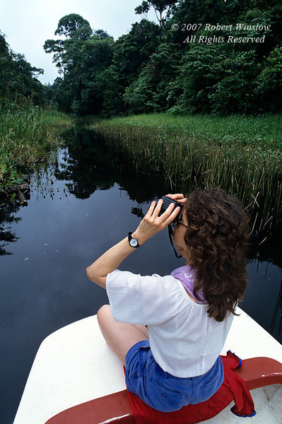 Model Released, Woman with Binoculars in a boat, Lake Coter, Lake Coter Eco Lodge, Private Biological Reserve, Northern Pacific Mountains, Arenal Lake Region, Costa Rica, Central America