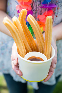 Woman Holding Paper Cup Filled With Churros And Chocolate Dip