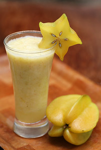 Carambolaor starfruit juice in a glass with ripe fruit