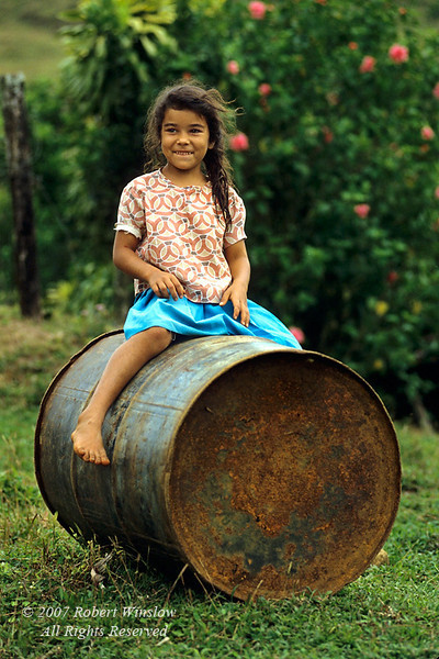 No Model Release, Young Girl in a blue skirt sitting on a 55 gallon drum, Arenal Region, Costa Rica, Central America