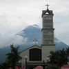 From the park in the center of La Fortuna you can see Volcano Arenal behind the church.