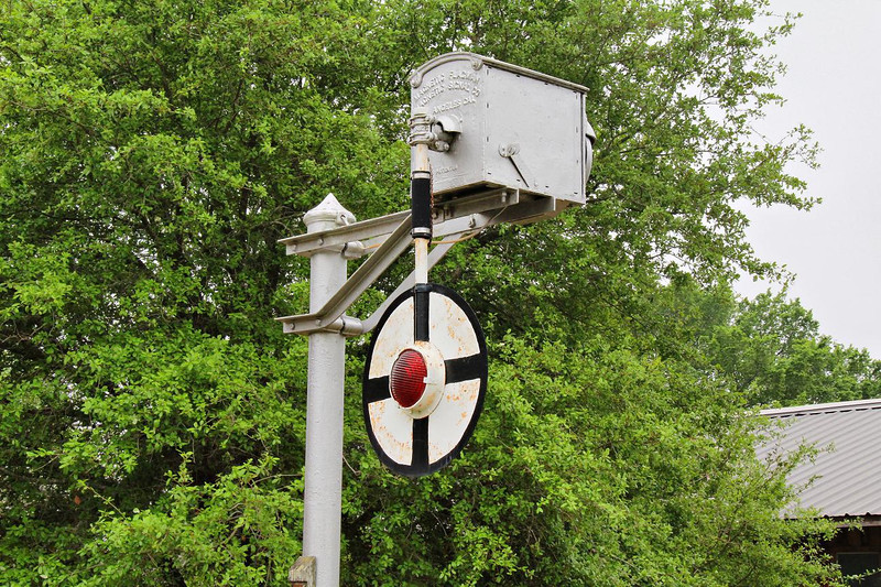 1914 wigwag signal (Magnetic Flagman) at Burton, Texas, April 2, 2011. Magnets swing the target back and forth and, once de-energized, the flag swings free until it slowly coasts to a stop. Nearby Brenham had one in daily use well into the mid 1990's, as did Vinton & Lake Charles, La. & Dayton, Texas. They were on the busy east-west main line that ran along the Interstate 10 corridor.