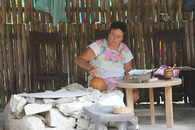 Mayan descendant making tortillas - they are kept warm in the gourd