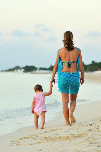 Mother walking with baby on beach