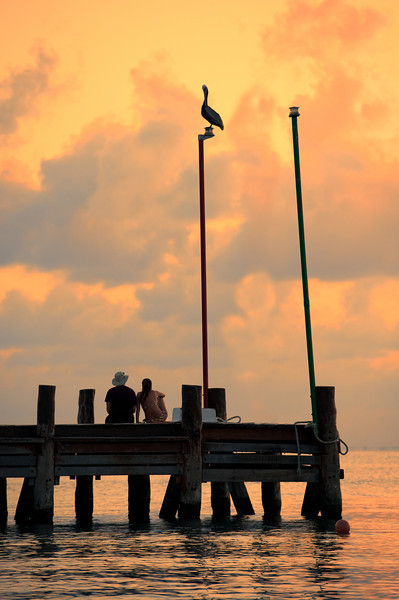Couple watching sunset from jetty in Cozumel