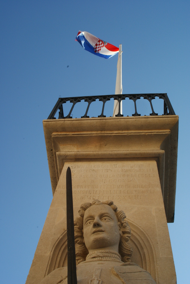 That's the Croatian flag.  That's a statue of a man looking at something big and pointy.