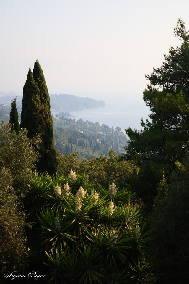 The Achilleion gardens on the hill look over the surrounding green hills and valleys and the Ionian sea.
