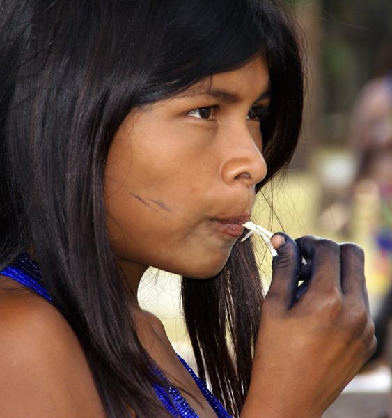 Embera girl eating sugar cane