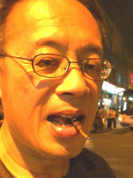 Beijing, China - Peter enjoying a deep fried scorpion.  Yum!