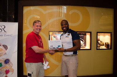"Kevin is presented with the ""free cruise"" certificate won at Bingo!"