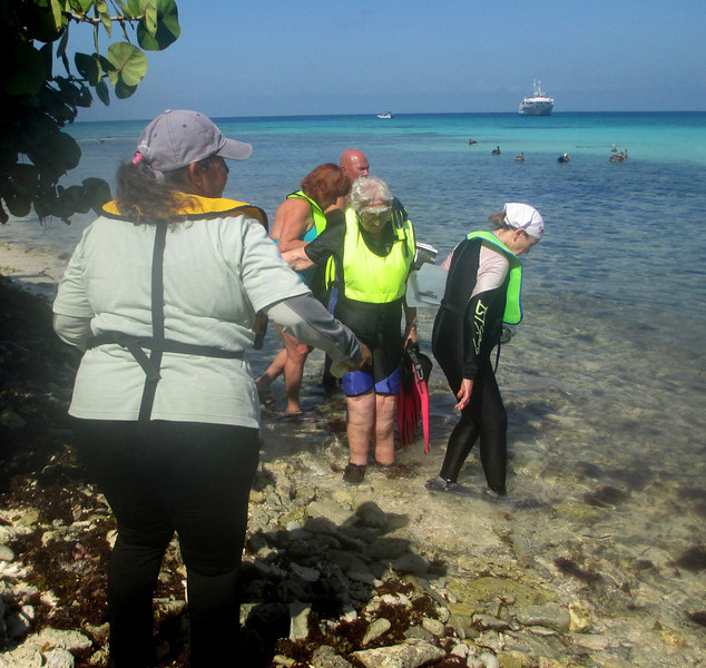 """Luz with snorkelers. Every snorkel excursion included a lecture with a plan for the excursion, any safety concerns, and a reminder to impact the sea life as little as possible. Most passengers, but not all, were avid snorkelers. Some had cruised with Blount on the Belize Barrier Reef cruise more than 10 times.<br /> <br /> """"Don't touch anything,"""" Luz (Luce) reminded us, """"anything you see, even litter, has already become a home for some creature!""""<br /> <br /> Our vessel, the Grande Mariner, hovers just off shore."""