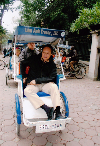 Hanoi, Vietnam - Peter as a passenger on a tricycle, a very common mode of transportation