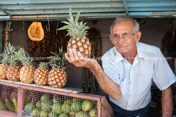 """Cuba, Trinidad, street scene.<br /> On the street fruiterer holds a pineapple for the camera.<br /> Prints & downloads.<br /> Model release; no.                also see;  <a href=""""http://www.blurb.com/b/3586795-cuba"""">http://www.blurb.com/b/3586795-cuba</a>"""