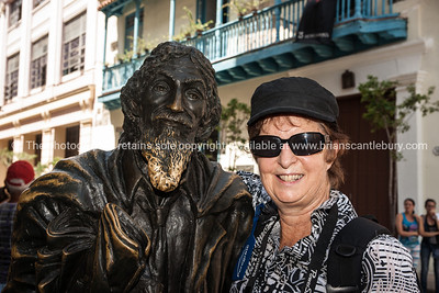 Tourist and the bronze statue of José María López Lledín.