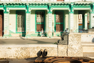 Pair old work boots propped up to catch early warm sun with dilipated green colonial build across street