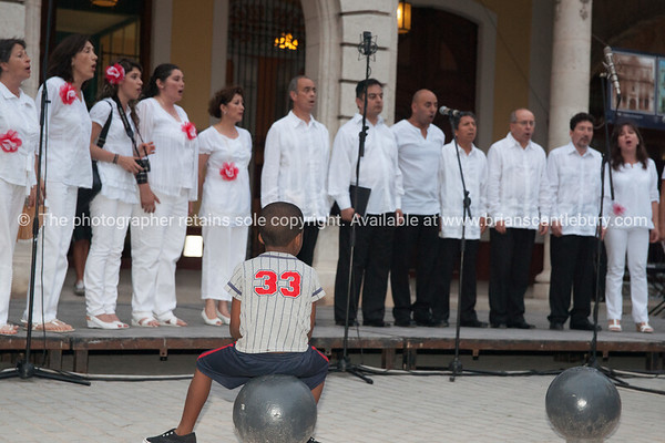 """Choir taking part in 2012 International Choral Competitions, Havana, Cuba, being watched by boy stiing on ball the the Viejos Square<br /> <br /> Prints & downloads.<br /> Model release; no.                also see;  <a href=""""http://www.blurb.com/b/3586795-cuba"""">http://www.blurb.com/b/3586795-cuba</a>"""