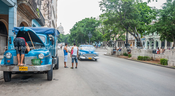 Two young men stand looking along street as car blurred in motion drives through and blue truck parked on roadside with bonnet up and person working on engine.