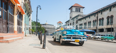 Bright blue convertible 1960's Chevrolet taxi in Havana street.