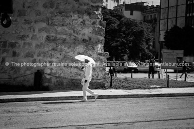 member of Santeria Cuban religious sect dress in all white walks along city street past old stone building