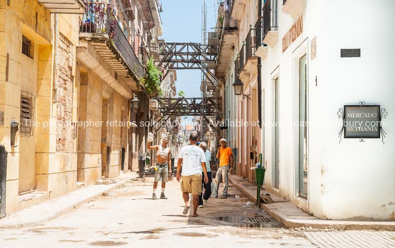 Workmaen in street undergoing significant restoration in Havana.