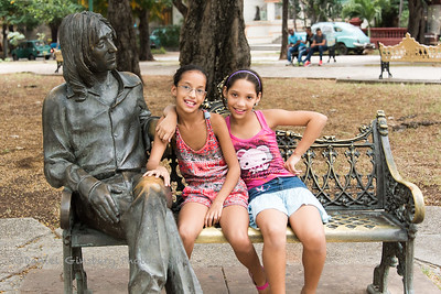 Two girls on John Lennon park bench sculpture in Havana, Cuba