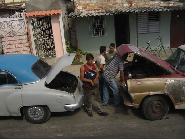Men fixing their old cars in Cuba