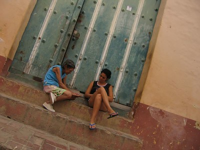 Old and young women on stairs in Trinidad, Cuba