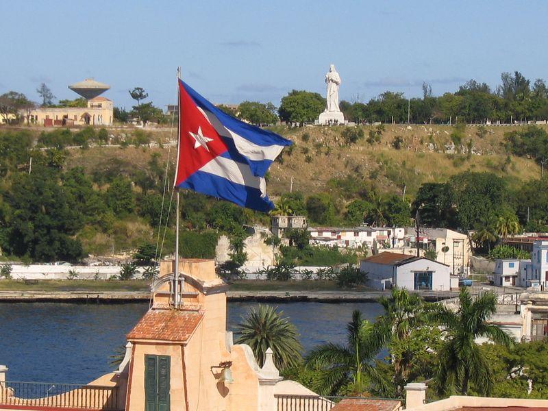 Cuban flag from rooftop bar overlooking city waterway in Havana, Cuba