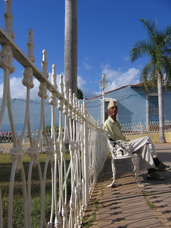 Fenceline and old man smokes cigar in Trinidad, Cuba
