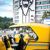 Little yellow bubble taxis with Che Guevara silhouette on the building in Revolution Square, Havana.