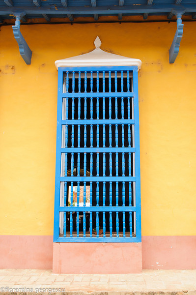 Facade of a typical house with wooden supports and window with barrotes, Trinidad, Cuba