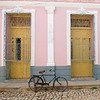 Typical pastel-colored house with wooden front doors framed by plaster motifs and wrought-iron ornamental grills, Trinidad, Cuba