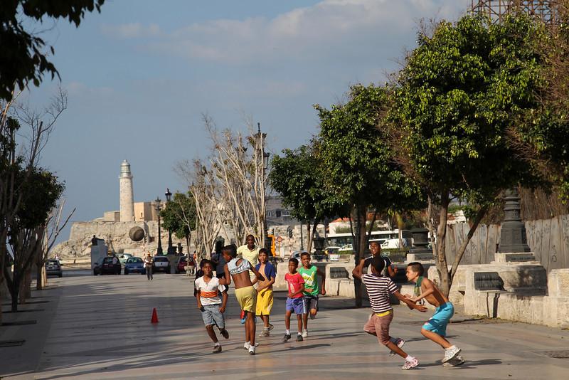 Boys play soccer on Paseo de Martí, the background is Morro Castle, Havana, Cuba,