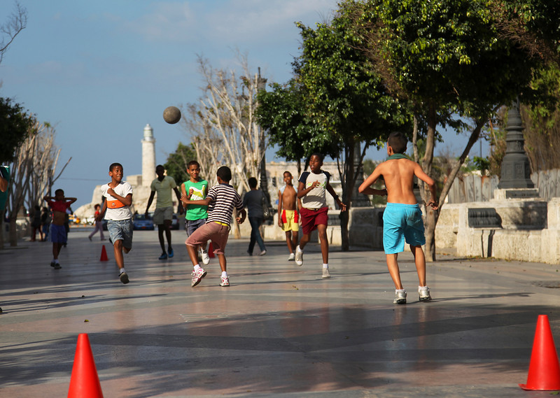 Boys play soccer on Paseo de Martí, the background is Morro Castle, Havana, Cuba,