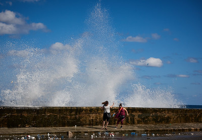 Tourists surprised by a big wave on the Malecón in Havana.