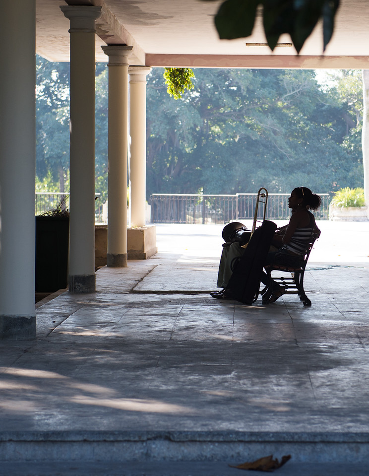 A trombone student sits outside at midday at the Cuban National Art School in Havana on March 11, 2014.