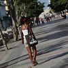 A woman is walking on Paseo de Martí, Havana with her dog.
