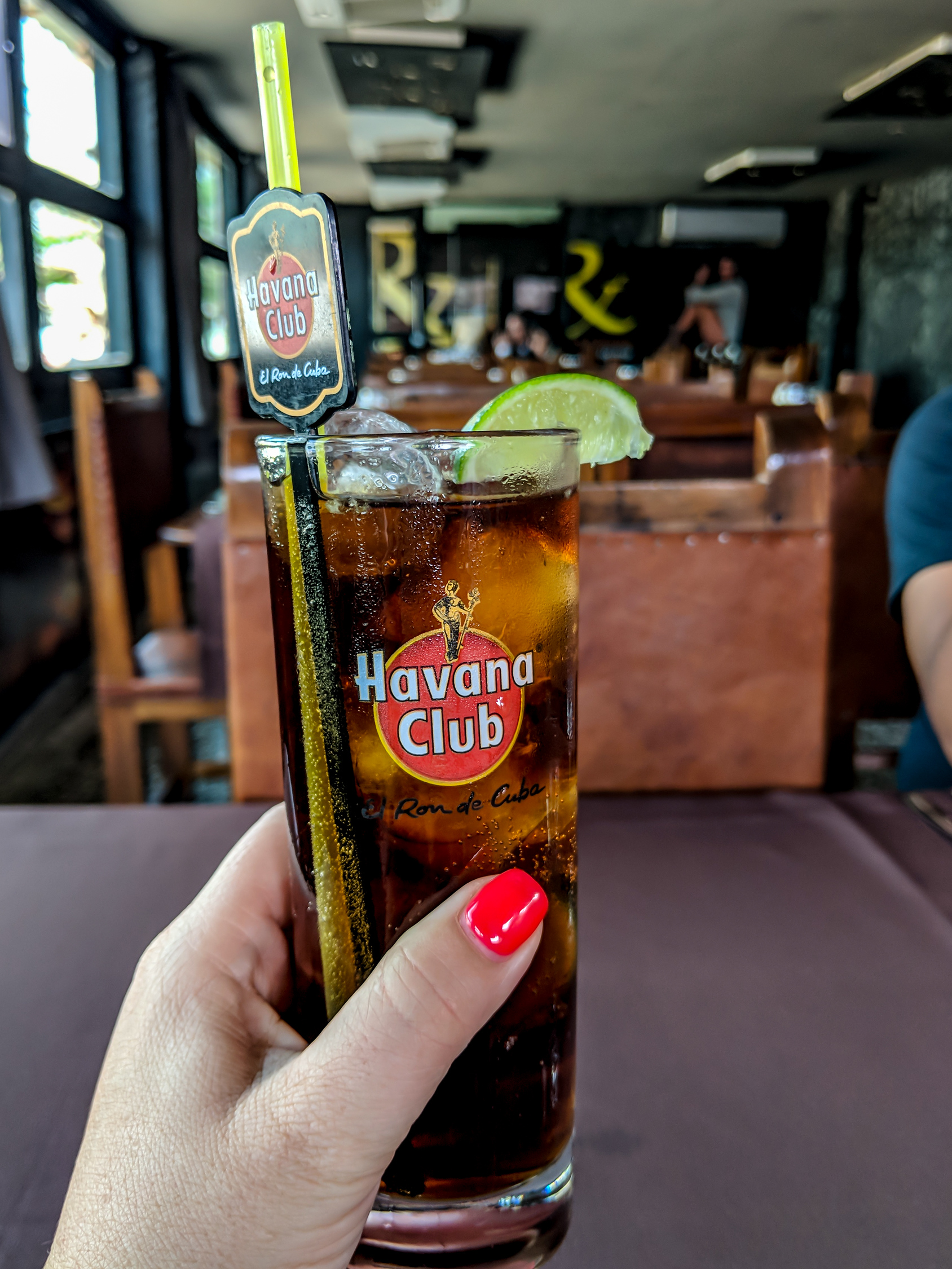 Cuban Cuba libre cocktail in a Havana Club tall glass.