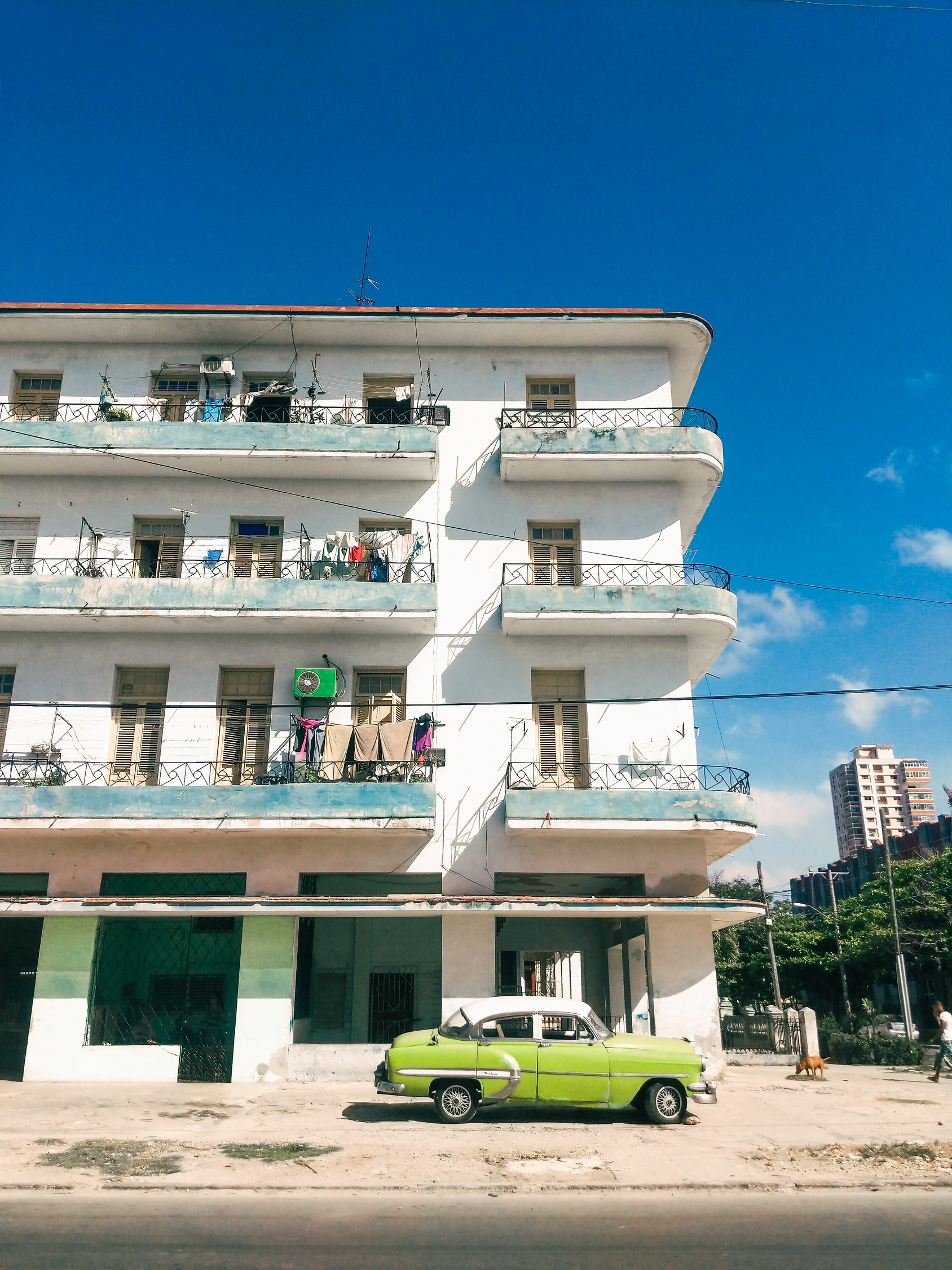 Antique green car outside building in Vedado Cuba