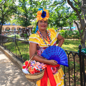 Cuban woman in colorful dress poses  in Plaza de Armas, La Habana Vieja, Old Havana, Cuba