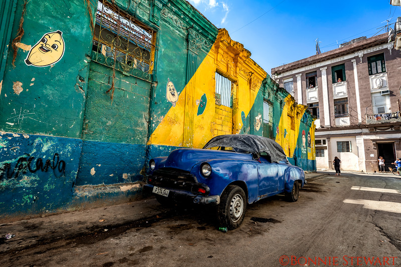 Classic car needing some work.  Political posters on the wall behind - Che and Castro