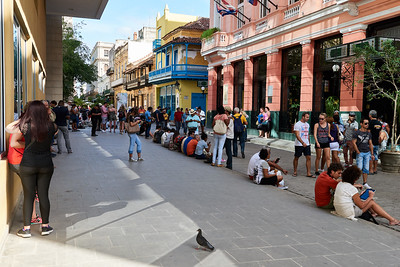 People enjoying a rare wifi hot-spot in front of a hotel, Havana.