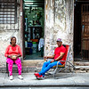 Cubans resting outside their home next to their neighbors on the right.