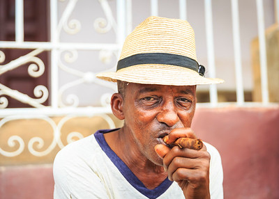 Portrait of man wearing straw fedora hat and smoking cigar in colonial Trinidad, Cuba