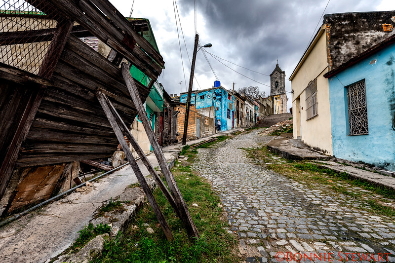 A neighborhood in Havana.   The house on the left is crumbling but reinforced by poles, the others up the street are in various stages of repair.